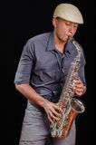 Black man playing the saxophone, feeling the music with white hat Royalty Free Stock Photos