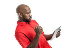 Black Man Playing on Tablet PC. Handsome African American man in his late 20s pumping fist excited playing on a tablet PC isolated on a white background Stock Photo
