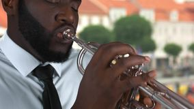 Black man playing trumpet. Musician on street background stock video footage