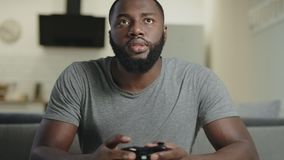 Black man playing video game at home. Portrait of black guy holding play station