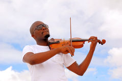 Black man playing violin. Outdoor portrait of an African American musician with black sunglasses and cool facial expression playing his violin in front of sky Royalty Free Stock Image
