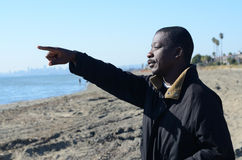 Black Man Pointing To The Ocean. At noon Royalty Free Stock Image