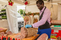 Black man preparing sausage at the market Royalty Free Stock Photos