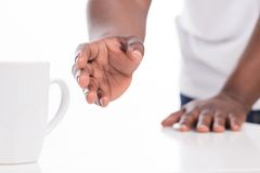 Black man reaching for cup. Royalty Free Stock Photography