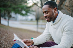 Black man reading book in park Royalty Free Stock Image