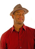 Black Man in a Red Shirt and Brown Hat Smirk. A black man in a red shirt and an old brown hat with a smile or smirk royalty free stock photo