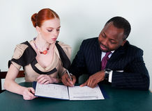 Black man and redhead girl with documentation. Black man and redhead young woman sitting with documentation stock photos
