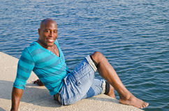 Black man relaxing at the edge of the pool. Royalty Free Stock Photography