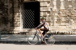 Black man riding a bicycle on a city street stock photo