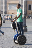 Black man riding blu segway Stock Photos