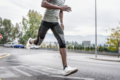 Black man running outdoors in urban road. Stock Images