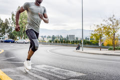 Black man running outdoors in urban road. Black man running outdoors in urban road listening to music with white headphones. Young male exercising with city Royalty Free Stock Image