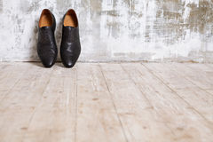Black man`s shoes against a wall in retro interior. Black men`s shoes against a wall in a retro interior in shades of gray Stock Photography