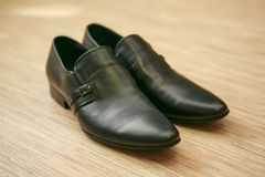 Black man's shoes. A couple of black man's shoes on wooden background Royalty Free Stock Images