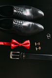 Black man`s shoes, cufflinks, wedding rings, a black belt and a. Red bow tie on a black background stock photos