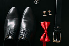 Black man`s shoes, cufflinks, wedding rings, a black belt and a Royalty Free Stock Images