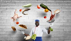 Black chef creative cooking. Mixed media. stock photos