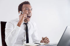 Black man shouting on phone. Furious african american businessperson sitting at office desk with laptop raising voice at interlocutor over the phone. Concept of Stock Image