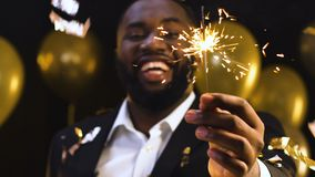 Black man showing bengal light to camera under falling confetti, New Year party. Stock footage stock footage
