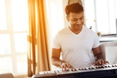 A black man sits in the living room of his apartment and plays a synthesizer. He composes music. Nearby is a gray laptop. A man likes to play music Royalty Free Stock Images