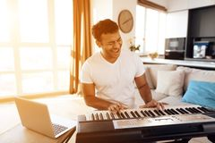A black man sits in the living room of his apartment and plays a synthesizer. He composes music. Nearby is a gray laptop. A man likes to play music Stock Photo