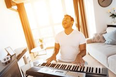 A black man sits in the living room of his apartment and plays a synthesizer. He composes music. Nearby is a gray laptop. A man likes to play music Royalty Free Stock Image