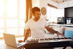A black man sits in the living room of his apartment and plays a synthesizer. He composes music. Nearby is a gray laptop. A man likes to play music Royalty Free Stock Photography