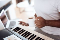 A black man sits in the living room of his apartment and plays a synthesizer. He composes music and drinks coffee. Nearby is a gray laptop. A man likes to play Stock Photos