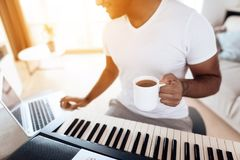 A black man sits in the living room of his apartment and plays a synthesizer. He composes music and drinks coffee. Nearby is a gray laptop. A man likes to play Stock Photo