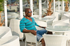 Black man sitting at a bar. Stock Image