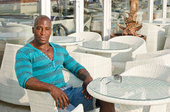 Black man sitting at a bar. Royalty Free Stock Photography