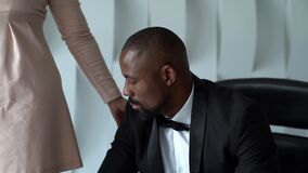 Black man is sitting on chair in white room, dressed in tuxedo, white woman is standing