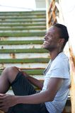 Black man sitting outdoors on stairs and laughing Stock Photography