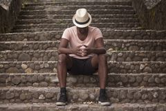 Black man sitting on a stairway of an old town royalty free stock images