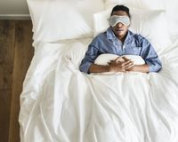 Black man sleeping on bed with eye mask royalty free stock photography