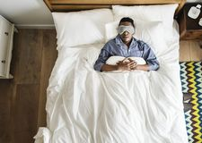 Black man sleeping on bed with eye mask royalty free stock images