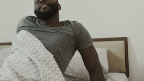 Black man sleeping in bed. Young male person waking up at bedroom slowly. stock video footage