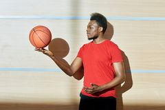 Black man spinning ball on fingers. African-American sportsman spinning basketball ball on fingers while standing near wall in gym Stock Photo