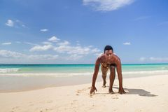 Black man in start position. At the beach Stock Images