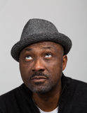 Black Man With Stubble Wearing A Hat looking Up. Portrait of a black man with a mustache and stubble beard wearing a hat looking up as if in thought isolated Royalty Free Stock Images