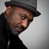Black Man With Stubble Wearing A Hat. Portrait of a black man with a stubble beard and a mustache wearing a hat and black cardigan isolated against a grey Royalty Free Stock Photo