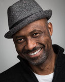 Black Man With Stubble Wearing A Hat. Portrait of a black man with a stubble beard and a mustache wearing a hat and black cardigan isolated against a grey Royalty Free Stock Images