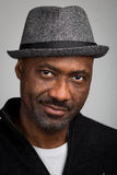 Black Man With Stubble Wearing A Hat. Portrait of a black man with a stubble beard and a mustache wearing a hat and black cardigan isolated against a grey Stock Image
