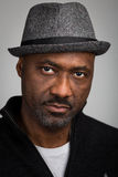 Black Man With Stubble Wearing A Hat. Portrait of a black man with a stubble beard and a mustache wearing a hat and black cardigan isolated against a grey Stock Photo