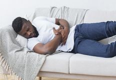Black man suffering from stomach ache at home. African-american man suffering from stomach ache, lying on sofa at home, closeup royalty free stock image