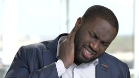 Black man in suit with neck pain.