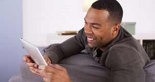 Black man surfing the web on tablet. Happy Black man surfing the web on tablet Stock Image