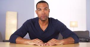 Black man at table looking to camera Royalty Free Stock Photo
