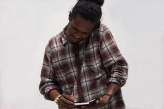 Black man taking notes while talking on phones, young papua man talk with smartphone while write on notes. Front view of black man taking notes while talking on royalty free stock image