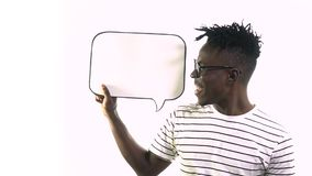 The black man is talking while looking at the dialog box that keeps nearby. Black hipster speak in the dialog cloud stock video